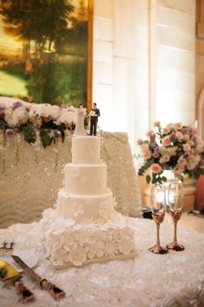 White 4 tier wedding cake with white fondant flowers http://www.fusion-events.ca/