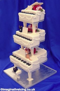 Melody (W151)(pianos)    A cake for music lovers. Cakes shaped as grand pianos and decorated with sugar blossoms round the sides. Sugar cats sit on the pianos and the stool. Silk flowers in the colour of your choice between the  pillars.The bottom tier and the stool are fixed to a gold or silver cake board.