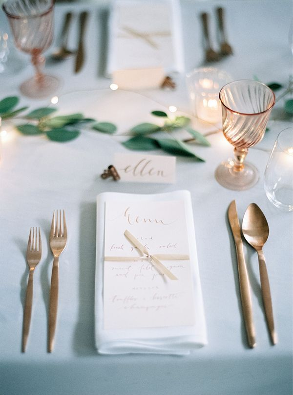 Elegant place setting with copper flatware and pink Depression glass