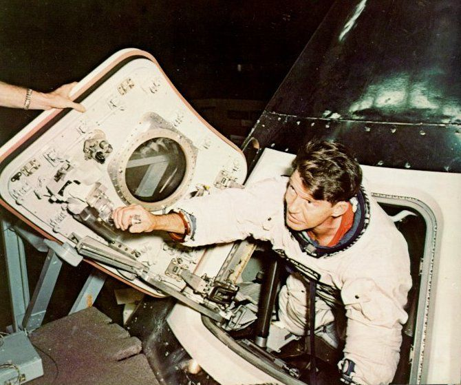 A photo of astronaut Wally Schirra inspecting the new hatch of the capsule