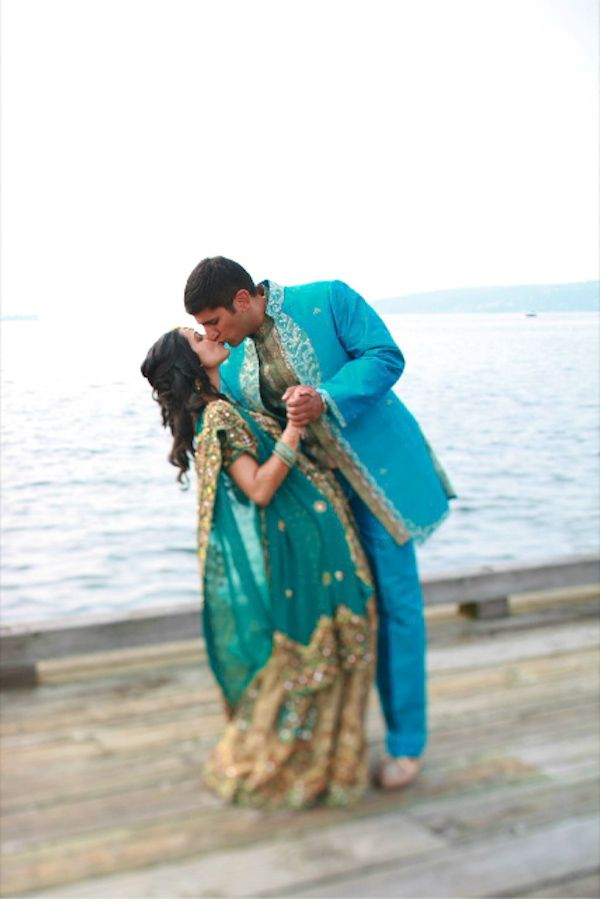 the happy couple kissing on the waterfront - alternative wedding apparel - aqua, teal and gold - photo by Seattle based wedding photographers One Thousand Words Photography