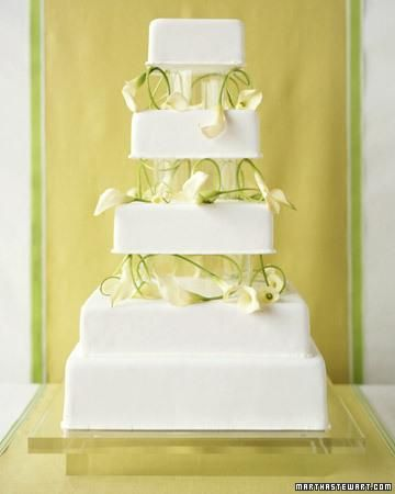 Miniature calla lilies, long and sinuous, are a dramatic counterpoint to crisp, angular tiers. Only the bottom layer of this glamorous structure, clad in white fondant, is meant to be eaten; the remaining tiers are Styrofoam, which keeps the flowers from touching the cake. Rubbing the stems between fingers renders them bendable. The tiers sit on clear acrylic columns and a custom stand.