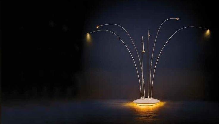 Los brazos cromados de la lámpara de pie Floora parten de su base iluminada para rematar en seis sutiles arcos, cuyas puntas se coronan con intensos focos de luz cálida, en Q Design Home.