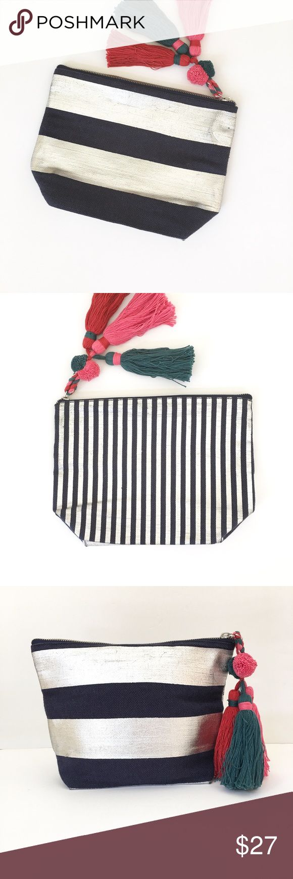 Anthropologie Metallic Stripes Clutch Shiraleah Chicago takes classic stripes and creates a bold statement with this beautiful clutch. Navy blue and metallic silver stripes are chunky and horizontal on one side and skinny and vertical on the other side.  An on-trend zipper pull has pom-poms and three chunky tassels creating a truly unique accessory for your wardrobe. Anthropologie Bags