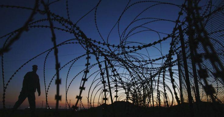 Soldado anda junto ao arame farpado em torno do Campo Delta na base naval americana de Guantánamo na Baía de Guantánamo, em Cuba