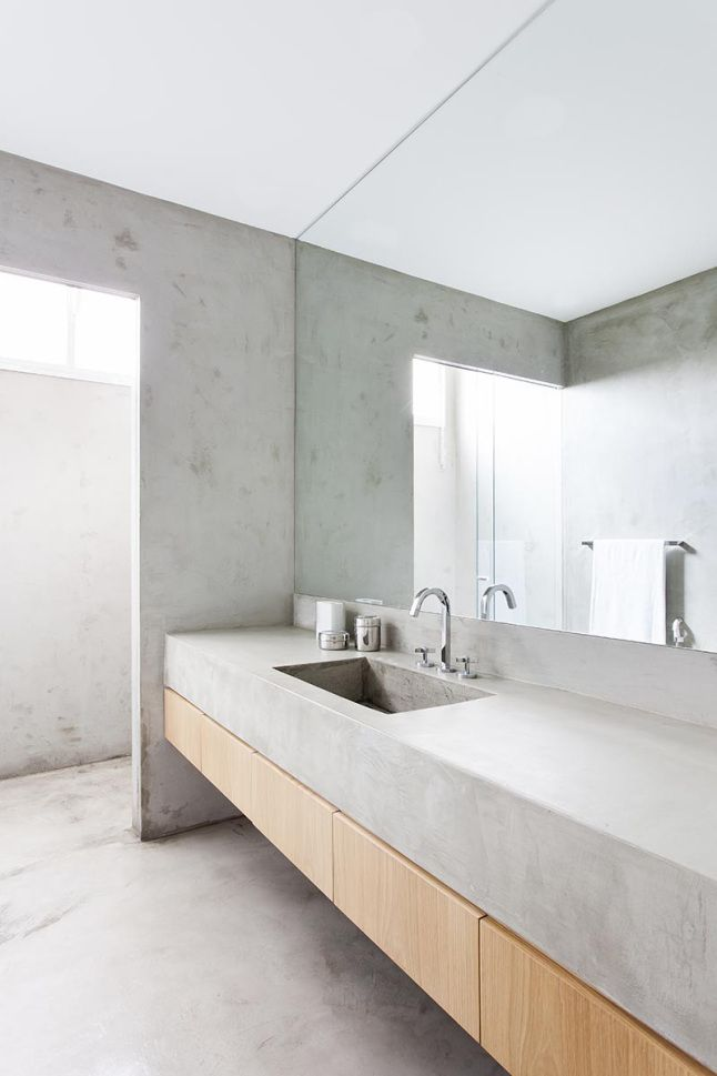 Light gray stone minimal bathroom with light wood drawers