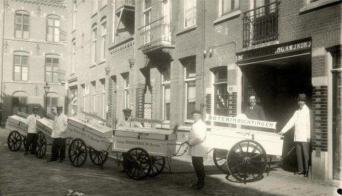 Vijf mannen in witte jassen met handkarren die deel uitmaken van de boterbezorgdienst van A.W.J. Kok in Haarlem. Nederland, 1919.