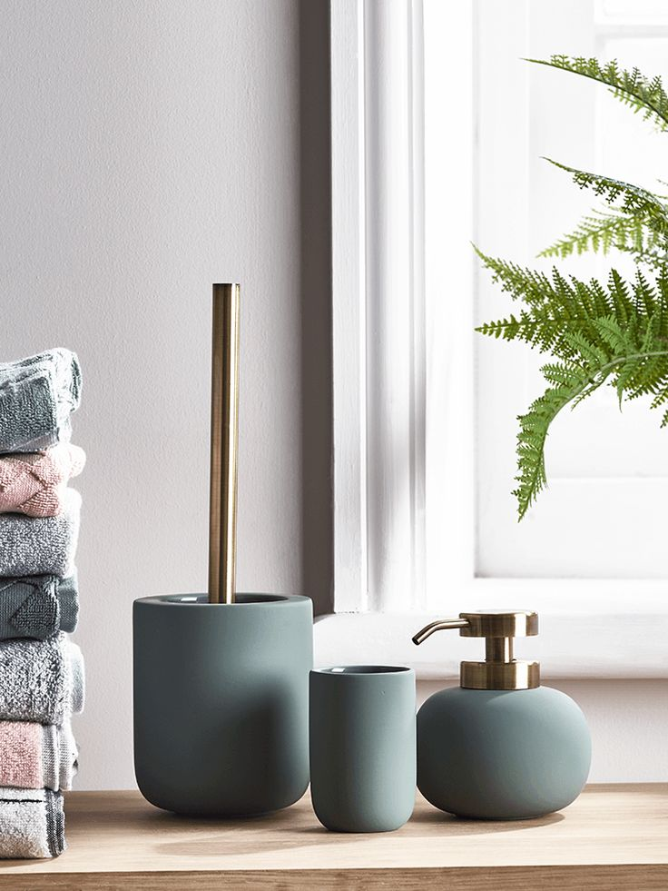 crafted from ceramic with a beautiful soft rubber finish and brass attachments our collection of muted smoke green bathroom accessories makes the perfect