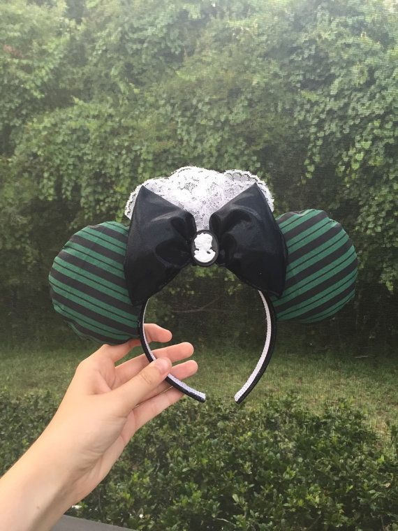 Spooky ears inspired by the Magic Kingdom ride Haunted Mansion! Ears are made with a custom-printed Haunted Mansion maids uniform fabric. The bow is
