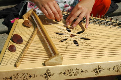 The Latvian kokle is a stringed instrument that is played while resting on the knees or on a table. One hand plays the tune, and the other hand muffles certain strings. The kokle can have varying numbers of strings, and its specific shape is determined by the particular design of Latvia's regions. (Vladimirs Koskins © 2006)