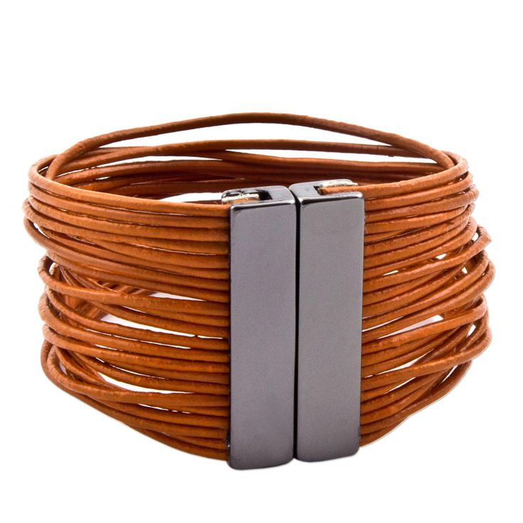 NOVICA Stainless Steel Leather Wristband Bracelet 'Burnt Orange Wires'. An original NOVICA fair trade product in association with National Geographic. Includes an official NOVICA Story Card certifying quality & authenticity. NOVICA works with Marilia Guimaraes to craft this item. Includes an original NOVICA jewelry pouch to keep for yourself or give as a gift. A keepsake treasure designed to be loved for years to come.