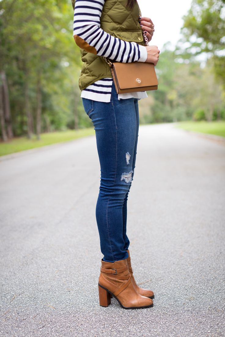 white and black striped shirt with brown elbow pads, army green quilted puffer vest, jeans, and brown ankle boots