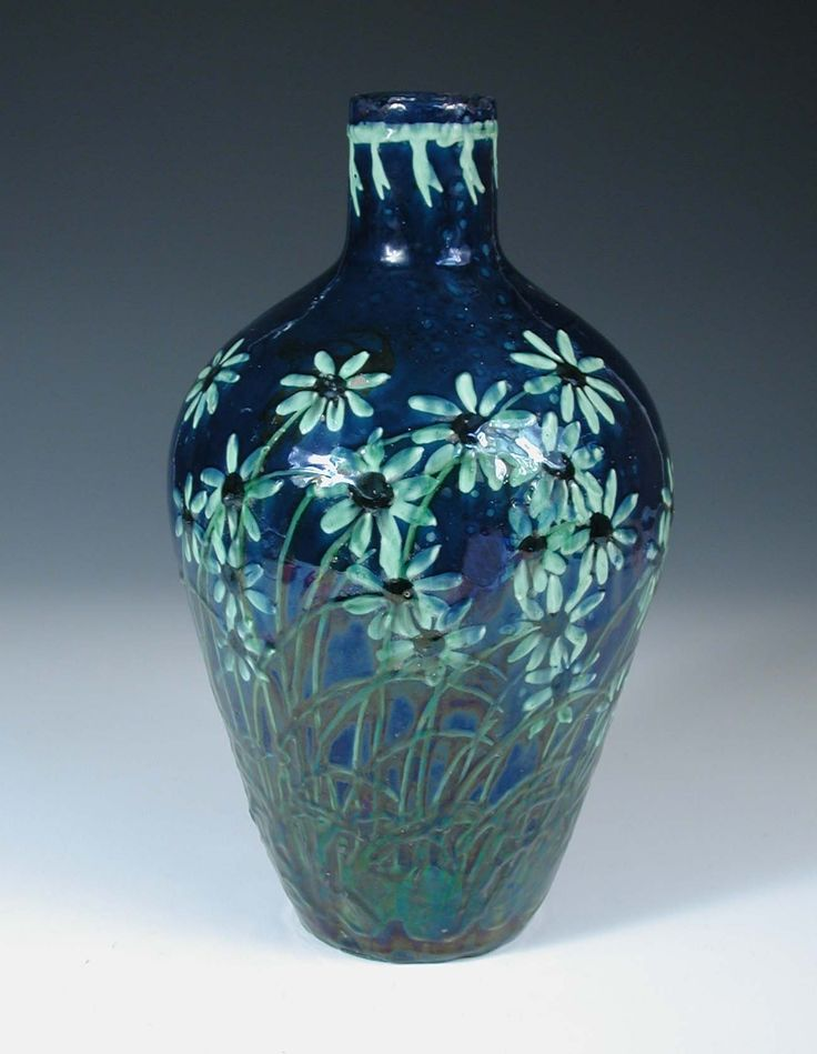 An earthenware vase by Professor Max Läuger, slip decorated with foliate design over deep blue ground