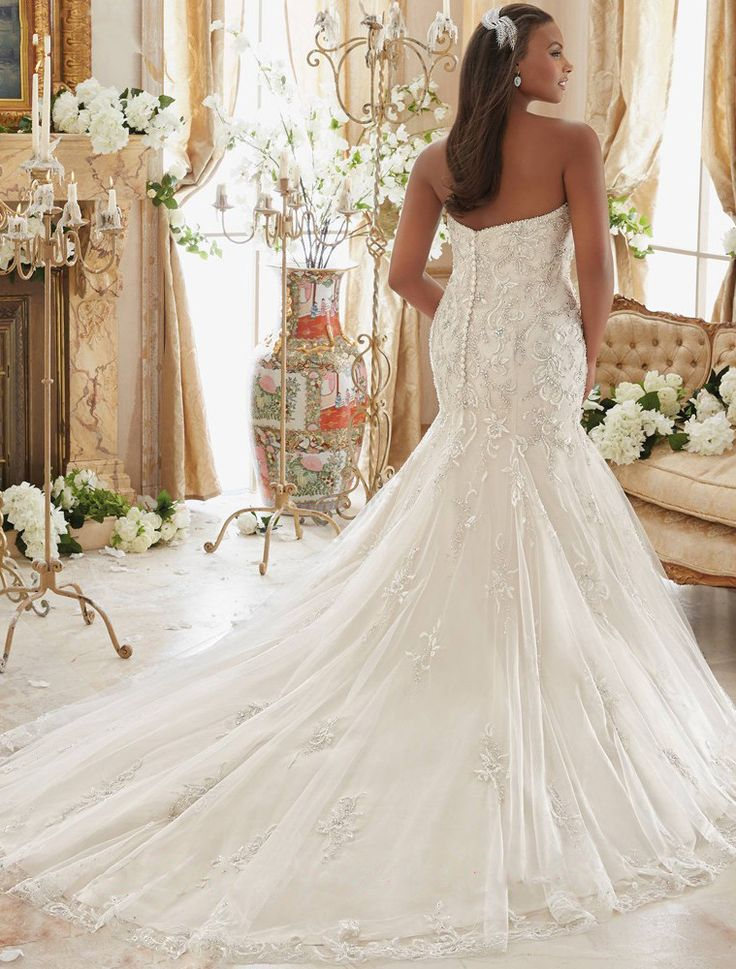 Gorgeous mermaid style gown with fishtail, chapel train. The sleeveless halter top wraps around to satin covered button-up back. The dress is embellished with lace appliques sprinkled with beads, sequ