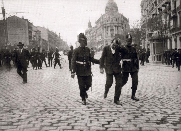 Detenciones tras la manifestación del 1º de Mayo de 1918. La manifestación había partido desde la plaza de Isabel II y había pasado por Arenal, Sol y Alcalá, hasta  llegar a la plaza de la Independencia donde estaba situada la tribuna de oradores. Estuvo encabezada por Pablo Iglesias y otros dirigentes socialistas. Al disolverse la manifestación se produjeron disturbios con el resultado de algunos heridos y nueve manifestantes detenidos.    Alcalá con Gran Vía