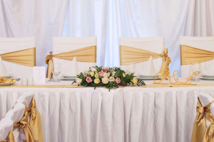 Hosszúkás virágdísz a főasztalra rózsából, rezgőből. Üde színvolt az arany-fehér esküvői dekorációban. Szeretnél hasonlót? Válogass eddigi munkáink közül: http://eskuvoidekor.com/viragdekoracio