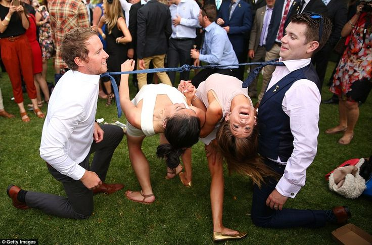 AUSTRALIAN RACE GOERS Two woman bend backwards between two racegoers who have their ties tied together as racegoers play a game of limbo