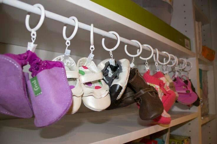 Tension rod and shower curtain clips to keep baby shoes organized.