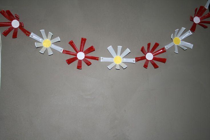 Je leefkamer mooi versieren voor een feestje? Hier mag zeker deze leuke bloemenslinger niet ontbreken!  Je hebt een zeer leuke slinger voor een verjaardag , trouw , geboorte , babyborrel ...     Benodigdheden :  * plastic bekers (in verschillende kleuren) * geel en wit papier * perforator * touw * lijm  1. knip je beker
