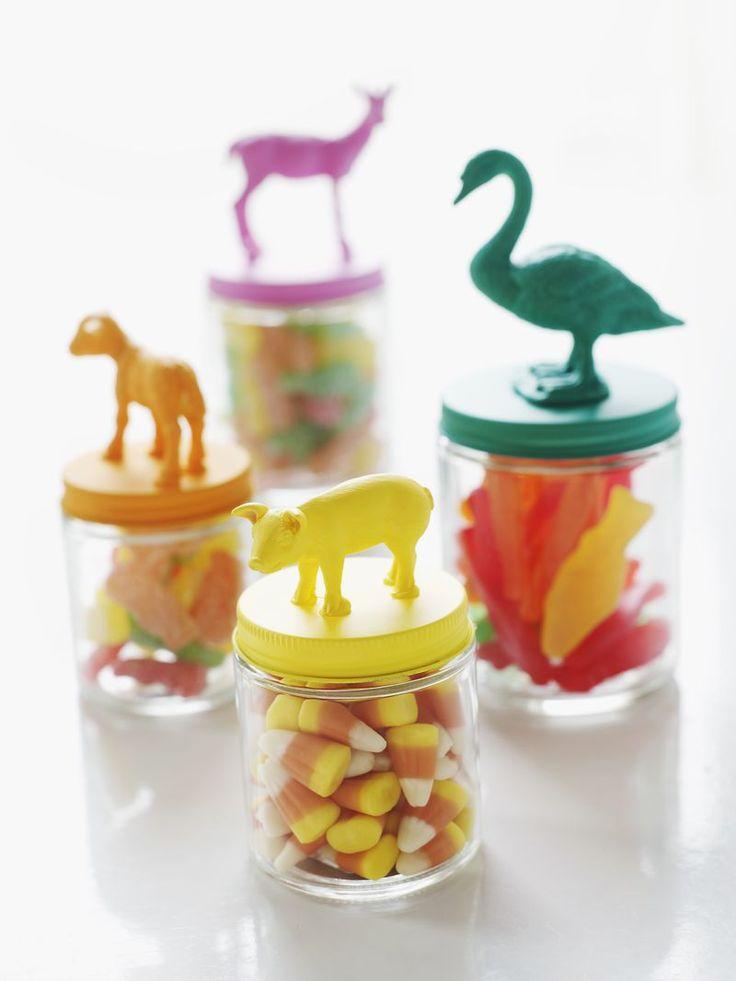 Peindre des figurines en forme d'animaux et les coller sur des couvercles de petits bocaux peints de la même couleur.
