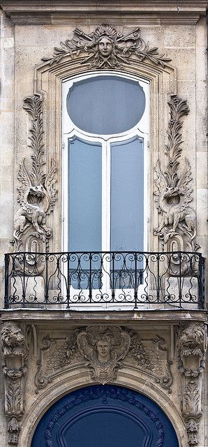 Wonderfully fun, exotic balcony and main doors with opulent carved surrounds in Paris.