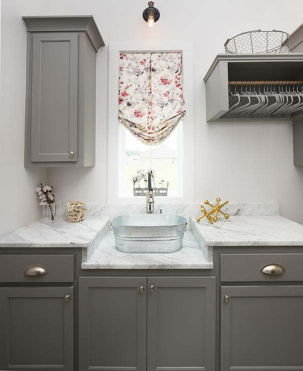Gray laundry room features gray cabinets paired with marble countertops lined with an oval bucket sink and a pull out faucet placed under a window dressed in a red and purple floral roman shade.
