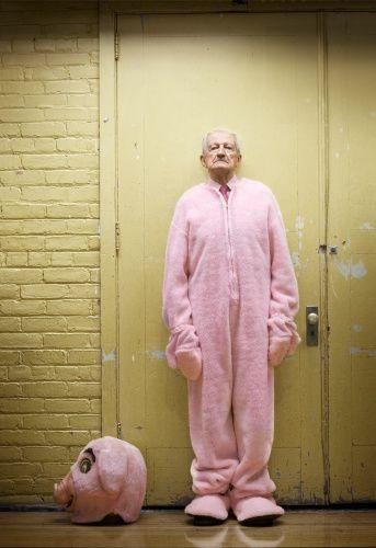 Stock-Foto : Senior man wearing pig mascot costume in gymnasium