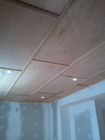 Finished basement ceiling – small plywood panels and wood battens. Maintain accessibility with minimal headroom loss, can be painted or stained/varnished