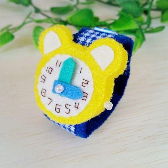 フェルトで作ったおもちゃの腕時計です。時計部分は可愛いクマ型で、文字盤の数字は全てひとつひとつ手刺繍しています。長針と短針はお好きな位置へ動かす事ができます。ベルトの着脱はボタンで、三段階の長さ調節が可能です。お子様のごっこ遊びや普段のお洒落、ディスプレイなどに。またプレゼントにもおすすめです。●カラー:時計部分…黄色   ベルト…青のギンガムチェック柄●サイズ:ベルト長さ 18cm●素材:フェルト、ビーズ、ファブリックテープ、ボンド●注意事項※小さなパーツや一部にボンドを使用していますので、お子様が口に入れたりしないよう充分にご注意ください。※時計の針は同じ方向に回し過ぎると、縫い止めている糸が切れたり、フェルトが傷んで破損の原因となりますので、同じ方向に一周以上回さないようにお願い致します。※出来るだけ丈夫に作ってはいますが、フェルトの性質上、またハンドメイド品のため市販品のような強度はありません。優しくお取り扱い頂けますようお願い致します。●制作者: gokko…