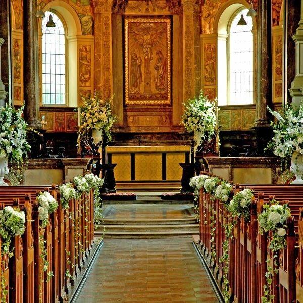 Composizioni floreali a cascata adornano questa chiesa per un matrimonio.