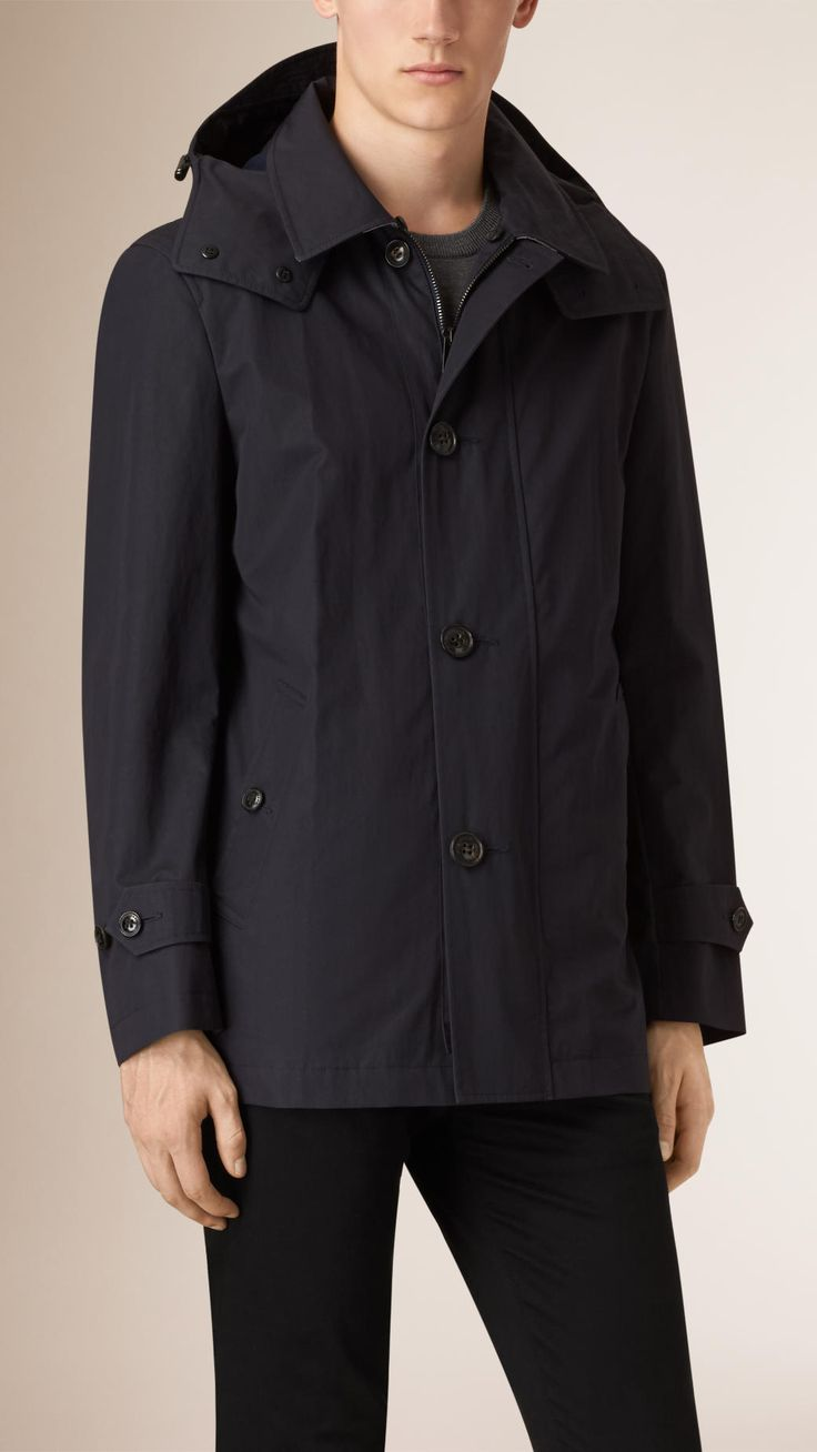 A showerproof jacket made from cotton blend with a tonal check undercollar. The structured design has a detachable hood with a guard and a button and zip closure for added protection against the elements.