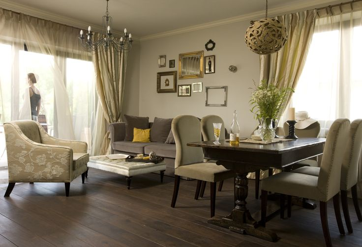 stylish living room with the wall decorated in carved frames, stylish armchair, floral stylish armchair, dark floor, living room with dining room, stylish chairs, antique table, antique table in stylish dining room, vintage dark table, vintage table