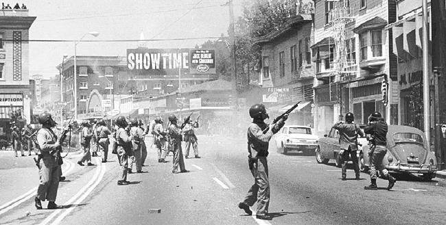 """People's Park """"Bloody Thursday,"""" Berkeley. 1969. Alameda County Sheriff's deputies used shotguns to fire """"00"""" buckshot at people sitting on the roof at the Telegraph Repertory Cinema, fatally wounding student James Rector and permanently blinding carpenter Alan Blanchard. The University of California Police Department (UCPD) claims Rector threw steel rebar down onto the police, however according to eyewitnesses, Rector was a bystander, not a protester."""