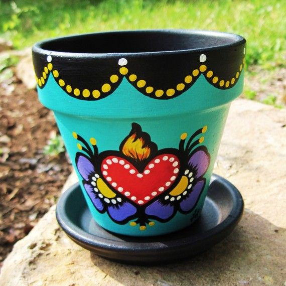 This listing is for an original flower pot, inspired by Mexican folk art and traditional tattoo design. This vibrant, teal pot is perfect for your favorite flower or plant! It features a flaming sacred heart, flanked by purple flowers. The inside of the pot and scalloped edging are solid black. The edging has been embellished with yellow and white dots. Its been matte sealed for indoor/outdoor use, and is waterproof. Theres a hole in the bottom for drainage, and it comes with a black dis...