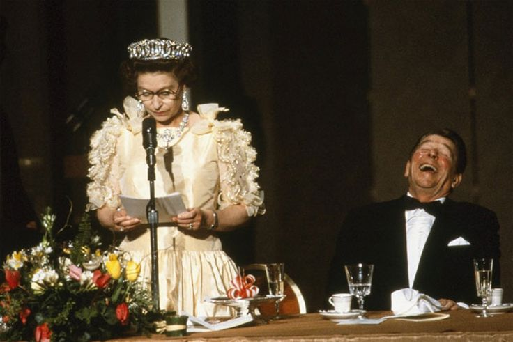 President Ronald Reagan laughing at a quip by Queen Elizabeth regarding weather during state dinner.