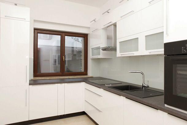 Biała kuchnia z wysoką zabudową szafek górnych