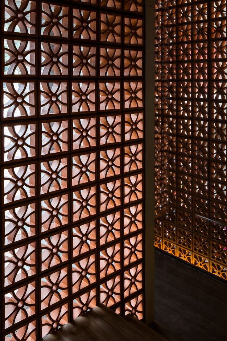These perforated blocks allow light to seep in gently. In daylight, they also form a canvas for different shadow patterns cast by tree foliage, while by night they allow the building to glow.