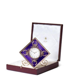 An enamelled silver-gilt desk clock by Fabergé, workmaster Michael Perchin, St. Petersburg, before 1899, of translucent amethyst enamel over sunburst guilloché ground, applied with four open laurel ribbon-tied crowns, within outer leaf palm rim, white opaque enamel dial with black Arabic chapters and gold Louis XV openwork hands within interwoven bezel.