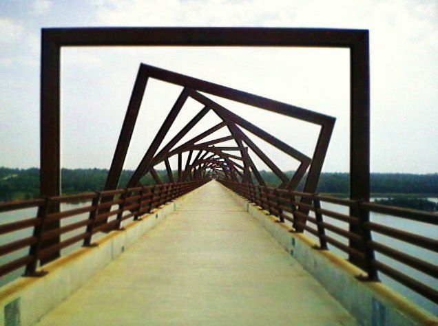 MAA Found Math: A spiral is formed as square structures rotate along the span of the High Trestle Trail bicycle bridge in central Iowa. The 41 steel structures that arch over the bridge were originally designed to represent the support cribs historically used in coal mines. Photo by M. E. (Murphy) Waggoner (Simpson College).