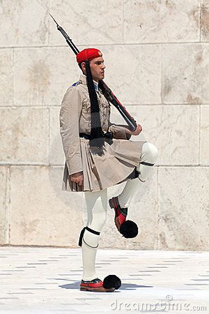 Evzones (presidential guards) watches over the monument of the Unknown Soldier in front of the Greek Parliament Building at Syntagma Square on July 23, 2010 in Athens, Greece. Evzoni, is the name of historical elite mountain units of Greek Army.