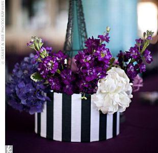 A black-and-white hat box, filled with purple and white blooms, surrounded a mini Eiffel Tower.