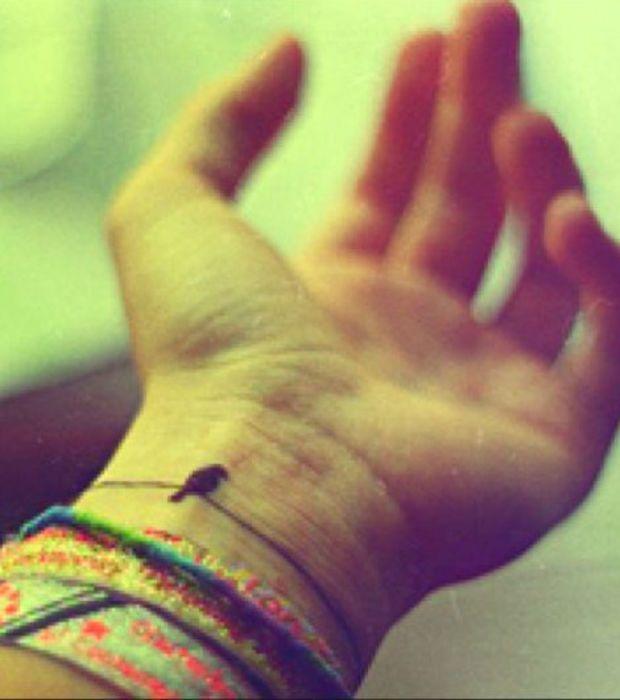 Photo : Un oiseau perché sur un fil tatoué dans le creux du poignet à la façon d'un bracelet