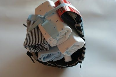 Love this idea for a baby boy shower - onesies rolled up in a baseball glove.