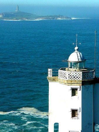 Faro de Punta Mera. Torre de Hércules lighthouse in the distance. La Coruña, Spain.