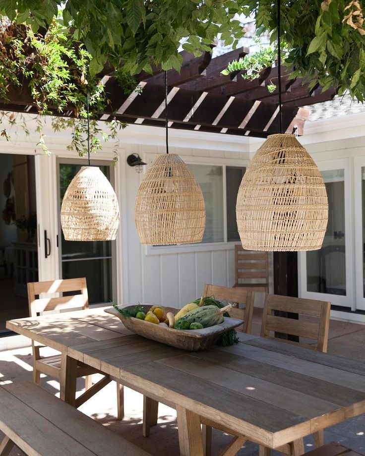 Pergola terrace with wooden dining table and wooden suspension. – Lampen