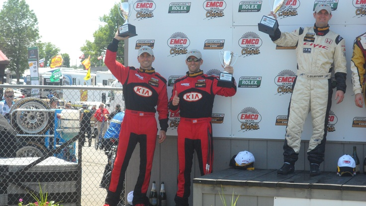 Kia Racing's Mark and Mathew Pombo stand tall on the podium at Mid-Ohio after a second-place finish in Round Five of the Continental Tire Sports Car Challenge.