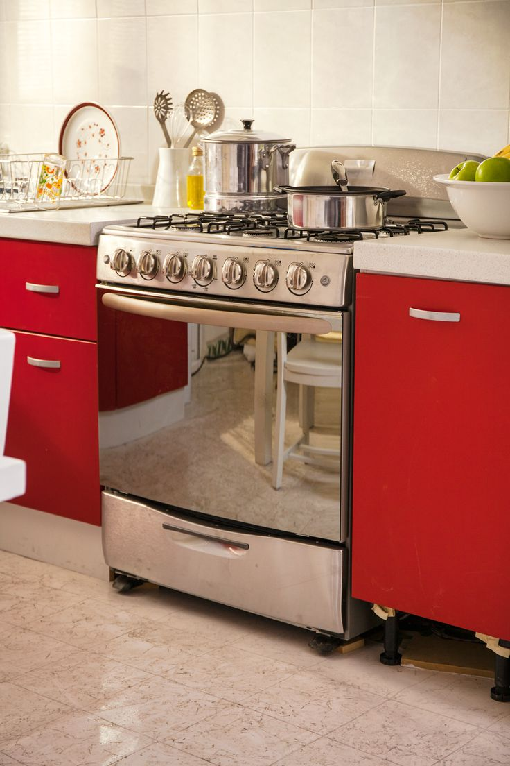 Combina una estufa de acero inoxidable con gabinetes rojos, dando un toque moderno.
