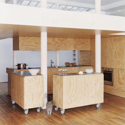 Cuisine conçue par les architectes Karine Chartier et Thomas Corbasson, composée de deux blocs en contreplaqué peint montés sur roulettes avec plan en inox : les deux plans peuvent se moduler en fonction des besoins, ce qui agrandit le salon ou vice versa