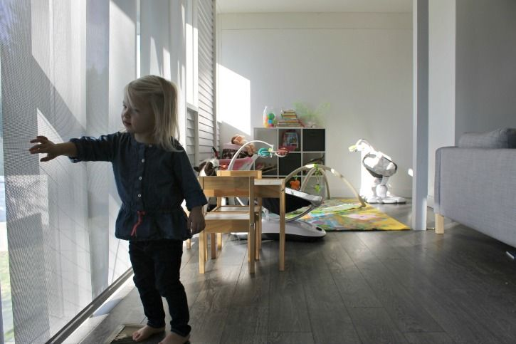 These gorgeous motorized solar shades fit this home's midcentury style perfectly AND they're safer for kids.