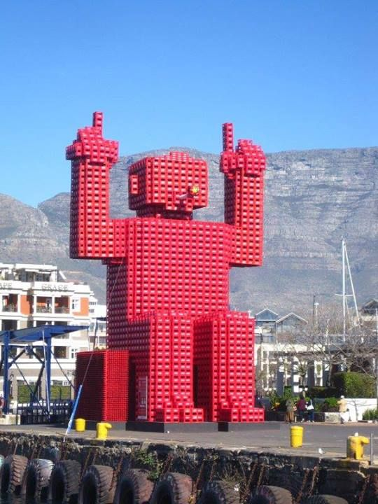 It's time to say goodbye to Elliot, Coca-Cola's crate man at the V Waterfront in Cape Town, as he's being packed up and crated away.  Designed to highlight Coke's recycling initiatives, it was built to be 15 metres high and made out of 2600 plastic Coke crates. Coke commissioned several crate men for South Africa but this one was the big daddy of them all.  Though Elliot will be missed, we can look forward to another Coca-Cola commissioned installation at V & A Waterfront soon!